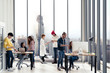 Successful multiethnic business team in routine work creative lifestyle standing, sitting and talking together at modern office with wide angle view. Young busy diverse teamwork or employees concept.