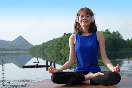 Aluminium School de yoga Young asian woman wear headphone and practicing yoga outdoors nature background