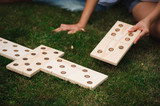 Young man and woman playing giant dominoes in the Park on the grass. - 212356695