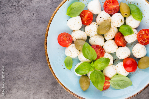 Delicious caprese salad with ripe cherry tomatoes and mini mozzarella cheese balls with fresh basil leaves. - 212371646