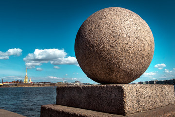 A granite ball is an element of the fencing of the Neva embankment on the background of the Peter and Paul Fortress. Stones St. Petersburg.