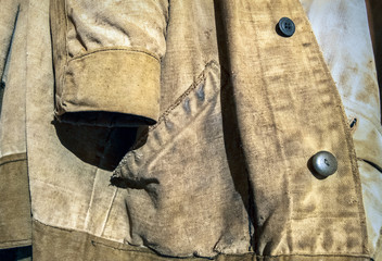 Old jacket of canvas.Special protective clothing of the welder from natural linen cloth hangs on the wall. He has scuffing damage, contamination and repair marks.