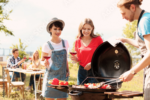 Leinwanddruck Bild Young people having barbecue with modern grill outdoors