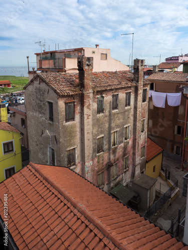Alley of Chioggia with an old house with brick chimney and sheets spread out to dry.