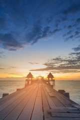 Wooden walking path with sunset over ocean skyline background