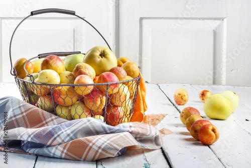 Leinwanddruck Bild Ripe tasty fresh apricots and apples in  woven metal basket