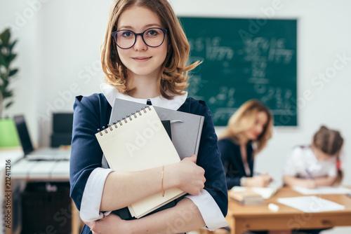 Portret uśmiechnięta szkolna dziewczyna z książkami w sala lekcyjnej