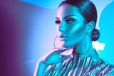 Fashion model brunette woman in colorful bright neon lights posing in studio. Beautiful sexy girl, trendy glowing makeup, metallic silver lips - 212412411