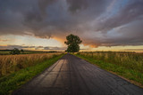 dramatic storm clouds over the road at sunrise - 212414250