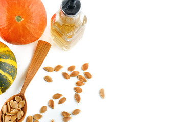 Fresh pumpkin oil isolated on white background. Flat lay, top view. Free space for text.