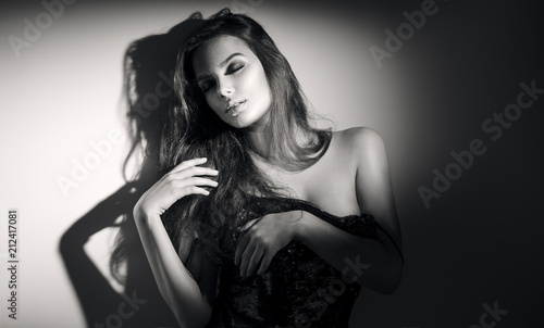 Leinwanddruck Bild Sexy young woman black and white portrait. Seductive young woman with long hair posing in spotlight