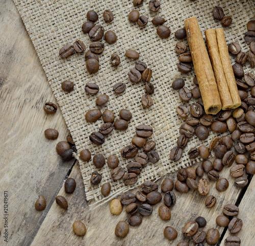 Aluminium Koffiebonen Coffee grains and cinnamon, on cloth and wooden table.