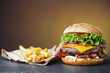 big cheeseburger with heap of french fries on slate board