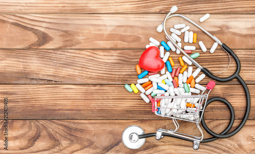 Fotobehang Apotheek Shopping cart with pills with red heart and stethoscope on wooden background. Space for text. Medical background. Top view.