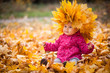 Little kid is playing and sitting in fallen leaves in autumn park. Baby is in big wreath of leaves. Girl is dressed in warm hat, jacket.