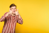 approving comic funny eccentric man showing thumbs up gesture. portrait of a young guy on yellow background. copyspace for advertisement. - 212438816