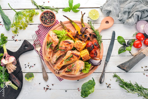 Baked chicken legs with spices and vegetables. On a wooden background. Top view. Copy space. - 212450808