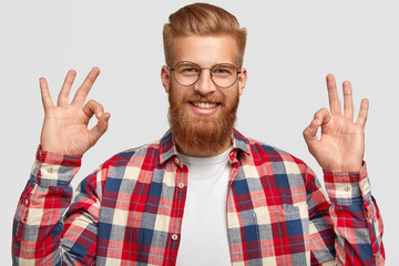 Handsome satisfied happy male likes somebody`s plan, shows okay sign, gestures in studio, has red thick beard and haircut, wears fashionable shirt. People, positive emotions and body language