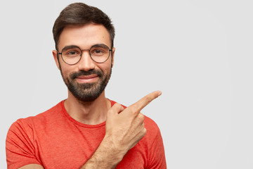 Photo of pleased unshaven European male with cheerful expression, has thick stubble, points aside, shows blank space for your advertising content, stands against white wall, dressed in red outfit © Wayhome Studio