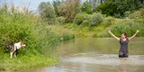 Frau steht in einem Gewässer, junger Hund am Ufer, Spaß und Lernen mit Welpe - 212457276