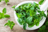 Fresh mint leaves in mortar bowl. - 212457476