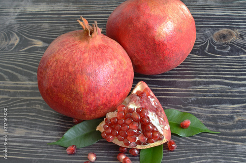 Foto Murales Red juicy fruit pomegranate with red seeds on black wooden background