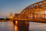 The illuminated Hohenzollern Bridge with the famous Cologne Cathedral after sunset
