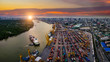 Leinwanddruck Bild - Aerial view of international port with Crane loading containers in import export business logistics with cityscape of Bangkok city Thailand at sunset