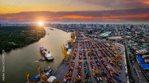 Leinwanddruck Bild Aerial view of international port with Crane loading containers in import export business logistics with cityscape of Bangkok city Thailand at sunset