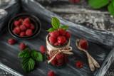 Raspberry in a glass jar on dark wooden background. Raspberry background. Healthy food concept. Fresh organic berries