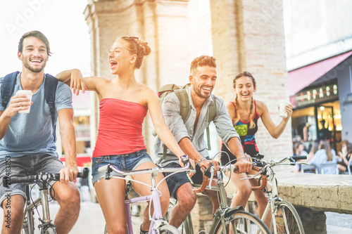 Happy friends riding bicycles in city center and drinking coffee - 212483853