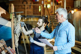 Aged engineer or master pointing at vessel and talking to his young colleague in workshop - 212485448