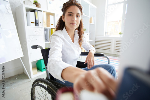 Wall mural Office worker in wheelchair taking book from shelf during working day in office
