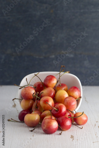 Fotobehang Kersen Bowl of Yellow and Red Cherries on a White Table with Slate Background