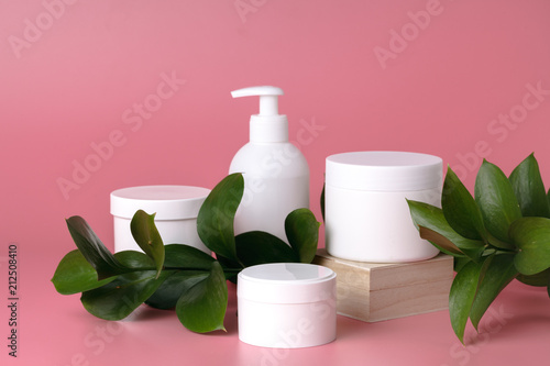 Cosmetic cream container and pink flowers on pink plaint  background