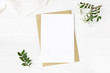 Feminine wedding stationery, desktop mock-up scene. Blank greeting card, craft envelope, baby's breath flowers, silk ribbon and lentisk branches. Old white wooden table background. Flat lay, top view.