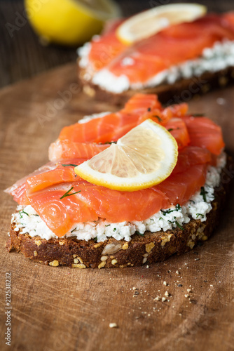 Tasty salmon sandwich with cream cheese and slice of lemon on wooden board, closeup view, selective focus - 212538232