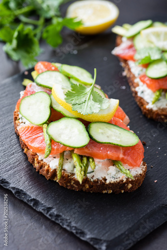 Fototapeta Sandwich with salmon, cream cheese and cucumber on slate background, closeup view, selective focus