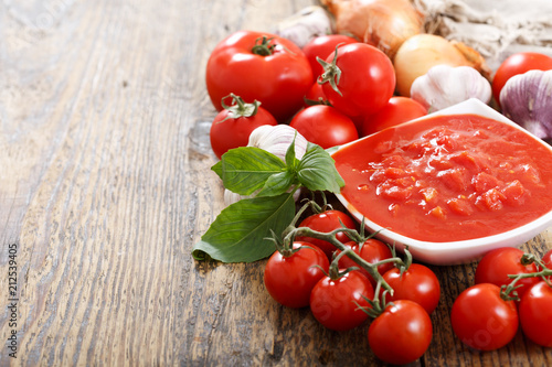 Wall mural bowl of tomato sauce with fresh vegetables