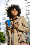 Favorite drink. Curly young woman in a trench coat visiting amusement park and holding a blue coffee cup - 212543670
