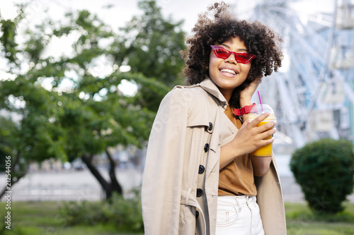 Aluminium Amusementspark Nice mood. Adorable curly woman in a trench coat holding a cup of orange juice and smiling a little bit bashfully while walking in the park