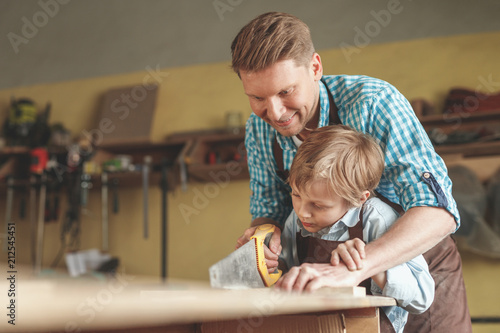 Father and son sawing a board indoors - 212545451