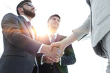 Close-up of business people shaking hands - 212548659