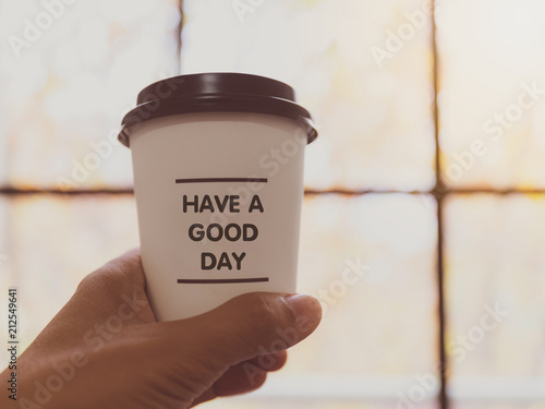 Poster Hand holding white coffee paper cup with text