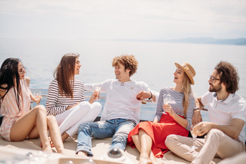 Two caucasian men invite three beautiful women to share pleasure yacht trip on the sea to islands, Young people laughing, enjoying amazing sea views