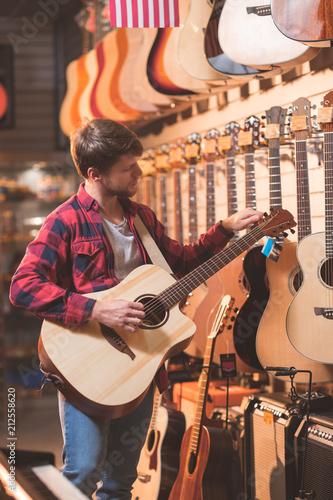 Fotobehang Muziek Young musician with a guitar indoors