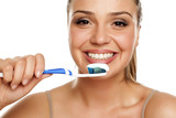 young smiling woman holding a toothbrush on white background - 212566020