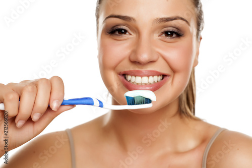 Leinwanddruck Bild young smiling woman holding a toothbrush on white background