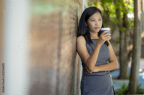 Poster Asian girls drink hot coffee in coffee shop