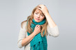 Beautiful young woman in knitted scarf suffering from headache standing against grey wall